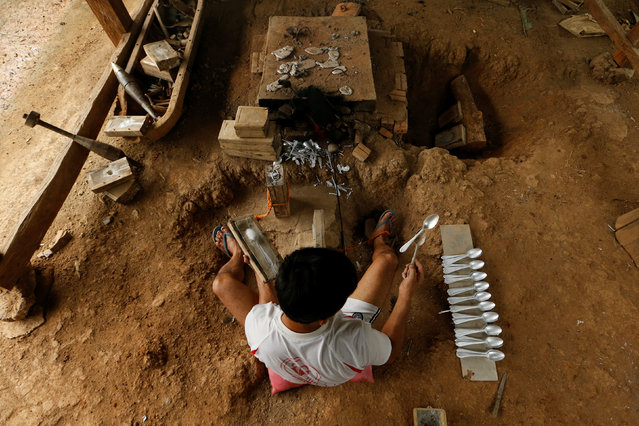 A man makes spoons by melting the bombs dropped by the U.S. Air Force planes during the Vietnam War, in the village of Ban Napia in Xieng Khouang province, Laos September 3, 2016. (Photo by Jorge Silva/Reuters)