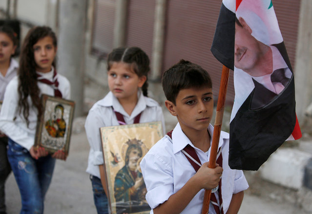 A boy carries a Syrian national flag depicting a picture of Syria's President Bashar al-Assad and girls carry icons of Virgin Mary during a parade, part of Saidnaya Festival, near Damascus, Syria September 7, 2016. (Photo by Omar Sanadiki/Reuters)