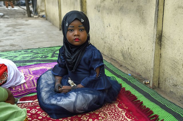 A young girl sits on a mat, as worshippers arrive to pray to mark the Muslim Eid-al-Adha (Festival of Sacrifices) without observationg precautionary measures to curb the spread of COVID-19, in Kara, Ogun State in southwest Nigeria, on July 31, 2020. Nigerian Muslim faithfuls joined their counterparts across the world to celebrate Eid-El-Adha, Islamic festival of sacrifice. (Photo by Pius Utomi Ekpei/AFP Photo)