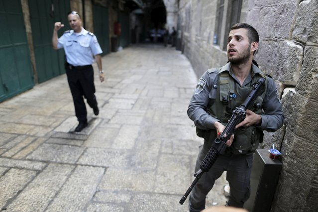 An Israeli border policeman holds his weapon as he guards following a stabbing attack in Jerusalem's Old City October 7, 2015. (Photo by Ammar Awad/Reuters)