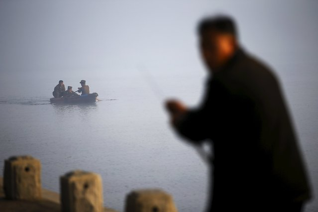 A man fishes as North Korean military personnel paddle a small boat amid morning fog over Taedong River in Pyongyang October 8, 2015. One of the world's most inaccessible places, North Korea has invited foreign journalists to Pyongyang this week for celebrations marking the 70th anniversary of its ruling Workers' Party, and rising wealth is evident despite a creaking state economy. (Photo by Damir Sagolj/Reuters)