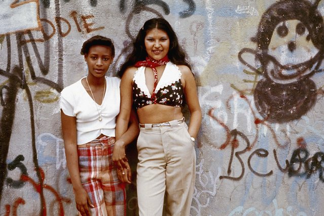 """Two Latin girls pose in front of a wall of graffiti in Lynch Park in Brooklyn, New York City, June 1974"". (Photo by Danny Lyon)"