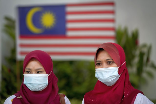 Malaysian women wearing face mask to help curb the spread of the coronavirus wait for the start of National Day rehearsals in Putrajaya, Malaysia, Friday, August 28, 2020. Federation of Malaya gained its independence from Britain on Aug. 31 in 1957. (Photo by Vincent Thian/AP Photo)