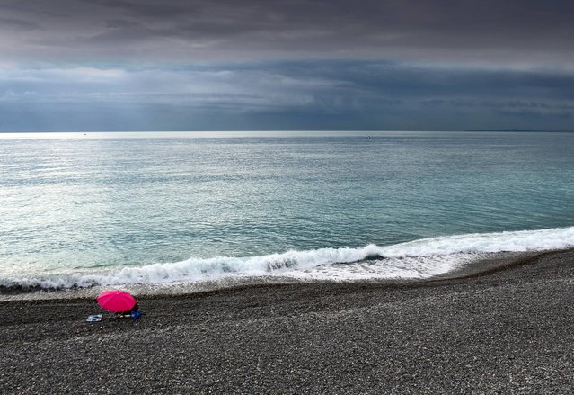 A man sunbathes under an umbrella on the beach of Nice, southeastern France, Friday, November 14, 2014. Temperatures in the area rose to 15 degrees Celsius (59 Fahrenheit). (Photo by Lionel Cironneau/AP Photo)