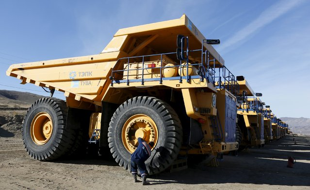 An employee services a 130-tonne BelAZ dump truck of the Mining Tuva Energy Industrial Corporation at the Zapadny coal opencast colliery of the Elegestskoye coal deposit outside the Ust-Elegest village in Tuva region, Southern Siberia, Russia, October 10, 2015. (Photo by Ilya Naymushin/Reuters)