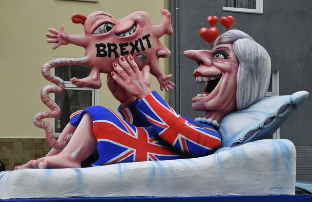 A float depicts British Prime Minister Theresa May looking at her Brexit-baby during the traditional Rose Monday parade in Duesseldorf, Germany, Shrove Monday, February 12, 2018. (Photo by Martin Meissner/AP Photo)