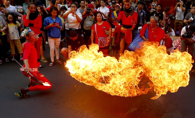 A fire-eater performs on the street in celebration of the Chinese Lunar New Year Friday, February 16, 2018 at Manila's Chinatown district, Philippines. This year is the Year of the Dog in the Chinese Lunar calendar. (Photo by Bullit Marquez/AP Photo)