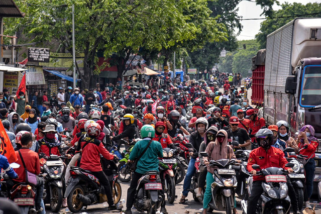 Laborers are seen demonstrating on the street against the labor law in Tangerang, Indonesia on October 6, 2020. This action represents workers' disappointment over passing of labor law in Indonesia is detrimental to workers. (Photo by Fransisco Carolio Hutama Gan/Barcroft Media via Getty Images)