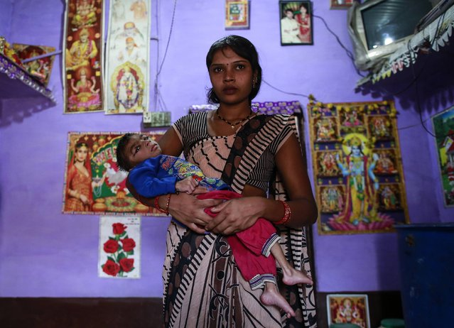 Five-year-old Saagar, who suffers from mental and physical disabilities is held by his mother Komal, as she poses for a picture at their house in a slum in Bhopal November 12, 2014. Saagar receives treatment at a rehabilitation centre supported by Bhopal Medical Appeal which only treats families they believe have been affected by the Union Carbide gas leak 30 years ago. (Photo by Danish Siddiqui/Reuters)
