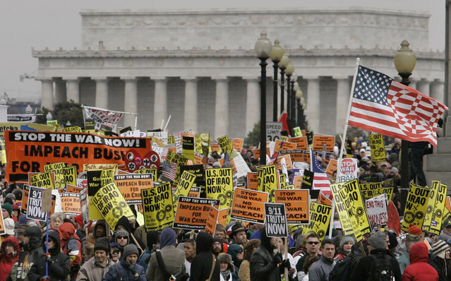 With the Lincoln Memorial in the background, demonstrators march over the Arlington Memorial Bridge from the National Mall to the Pentagon in Washington, on March 17, 2007 during a protest opposing the war in Iraq. (Photo by Gerald Herbert/AP Photo/The Atlantic)