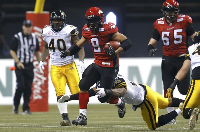 Calgary Stampeders' Jon Cornish tries to break away from Hamilton Tiger Cats' Simoni Lawrence during the first half of the CFL's 102nd Grey Cup football championship in Vancouver, British Columbia, November 30, 2014. (Photo by Todd Korol/Reuters)