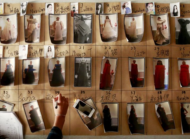 A staff arranges photos of models in their clothes backstage before the fashion show of ECHO CHEN Collection at China Fashion Week S/S 2016 in Beijing, October 26, 2015. (Photo by Kim Kyung-Hoon/Reuters)