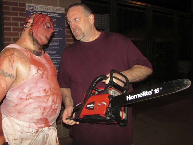 "Ted Corcoran (R) of Oklahoma City stands outside the Bricktown Haunted Warehouse with ""chainsaw guy"" actor Marcus ""Panda"" Bagwell (L) in Oklahoma City, Oklahoma October 25, 2015. Corcoran was one of the blind or visually impaired people who toured the haunted house in a visit arranged by NewView Oklahoma, one of the state's largest agencies for the visually impaired and blind. (Photo by Heide Brandes/Reuters)"