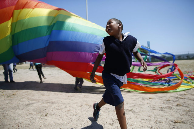 South African children from the Cape Mental Health Special Care centre play with kites as part of a special preview showcase for the Cape Town International Kite Festival in Khayelitsha, South Africa, 29 October 2015. International kite flyers from United Kingdom, Germany, Netherlands and South Africa assited disadvantaged and handicapped children to fly kites during this annual event. (Photo by Nic Bothma/EPA)