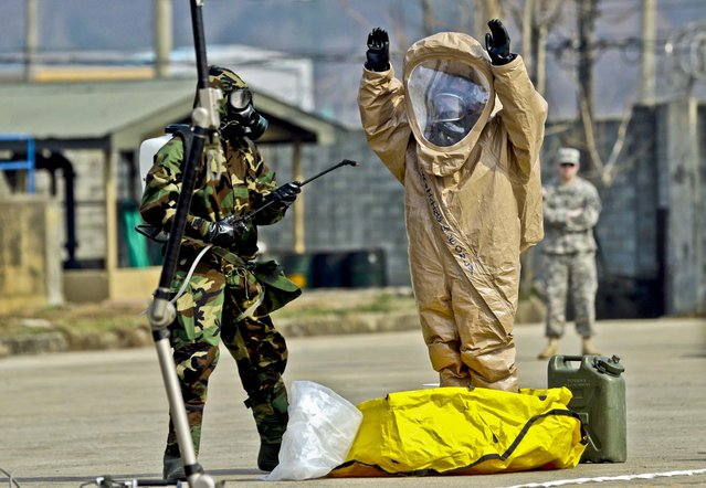U.S. Army soldiers conduct a demonstration of their equipment at a ceremony to recognize the battalion's official return to  Camp Stanley, north of Seoul, on April 4, 2013. The 23rd chemical battalion left South Korea in 2004 and returned with some 350 soldiers in January. The soldiers will provide nuclear, biological and chemical detection, equipment decontamination and consequence management assistance to support the U.S. and South Korean military forces. (Photo by Lee Jin-man/Associated Press)