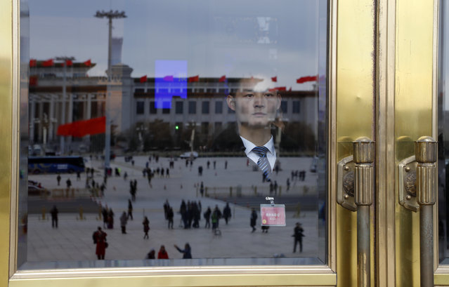 National Museum of China is reflected on a glass of the main entrance of the Great Hall of the People guarded by a security personnel during the closing session of the Chinese People's Political Consultative Conference (CPPCC) in Beijing, Thursday, March 15, 2018. (Photo by Aijaz Rahi/AP Photo)