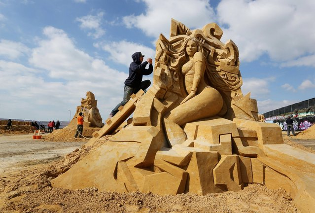 """Sculptor Barney Trattles puts the final touches to his music themed sand sculpture ahead of the start of the """"Sing-a-Song of Sculpture"""" festival in Brighton, on April 6, 2013. (Photo by Gareth Fuller/PA Wire)"""