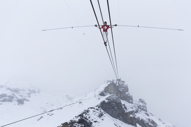 Swiss tightrope artist Freddy Nock walks on a rope towards the Schilthorn in the Bernaise alps, Switzerland, December 10, 2014. (Photo by Peter Klaunzer/EPA)