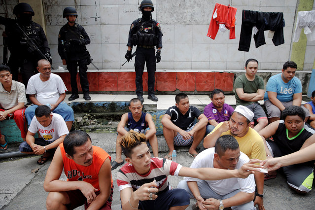 Members of the police SWAT team stand guard near residents who were rounded up, after police sources and local media reported that people were killed during a drug raid, in Manila, Philippines, October 7, 2016. (Photo by Damir Sagolj/Reuters)