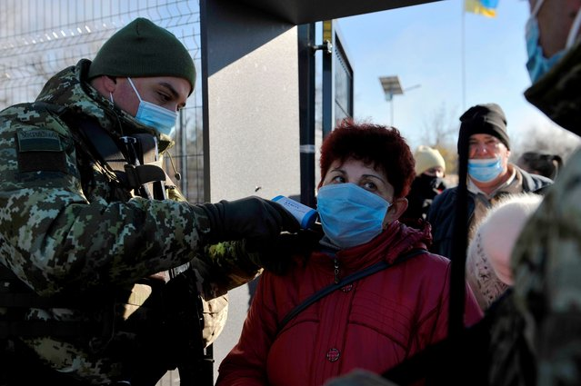 A Ukrainian border guard checks the temperature of a woman crossing the border at the checkpoint in the town of Schastya in Lugansk region on November 10, 2020. Ukraine opened on November 10, 2020, two new crossing points in the war-torn east but its attempt to facilitate the movement of civilians was hampered by separatists who denied passage to people. After a separatist uprising broke out in eastern Ukraine in 2014 and pro-Russian separatists carved out the Donetsk People's Republic and Lugansk People's Republic, travelling from and to Kiev-controlled territory has become a complicated affair. (Photo by Evgeniya Maksymova/AFP Photo)