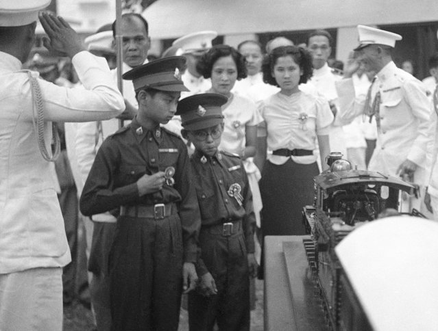 In this December 16, 1938, file photo, thirteen-year-old King Ananda of Siam, now known as Thailand, left, and his brother Prince Bhumibol, right, inspect a model train presented to him at Saranromya Gardens in Bangkok. Thailand's Royal Palace said on Thursday, October 13, 2016, that Thailand's King Bhumibol Adulyadej, the world's longest-reigning monarch, has died at age 88. (Photo by AP Photo)