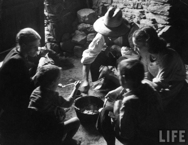 The Curiels eat thick bean and potato soup from common pot on dirt floor of their kitchen. The father, mother and four children all share the one bedroom. (Photo by W. Eugene Smith/Time & Life Pictures)