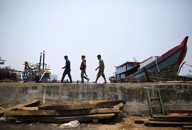 Men walk along the sea wall in Muara Baru, north Jakarta, September 30, 2014. (Photo by Darren Whiteside/Reuters)