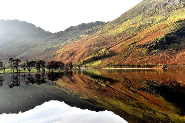 Autumn reflections are seen on Lake Buttermere in the Lake District in Cumbria on October 29, 2014, as the unseasonably mild weather continues. (Photo by Owen Humphreys/PA Wire)