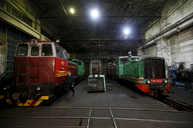 An engine driver's assistant walks past Soviet narrow-gauge diesel locomotives TU7 and TU4 at a train depot in Alapayevsk in Sverdlovsk region, Russia, October 15, 2015. (Photo by Maxim Zmeyev/Reuters)