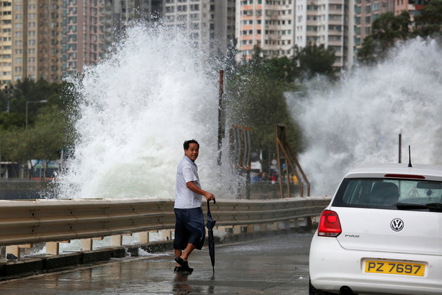 A man looks on while walking in front of big waves along a waterfront as Typhoon Haima approaches in Hong Kong, China, October 21, 2016. (Photo by Bobby Yip/Reuters)