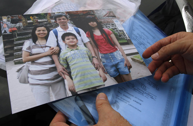 A relative shows a photo of four members of a family who were passengers of AirAsia Flight 8501, at the crisis center at Juanda International Airport in Surabaya, East Java, Indonesia, Wednesday, December 31, 2014. (Photo by Firdia Lisnawati/AP Photo)