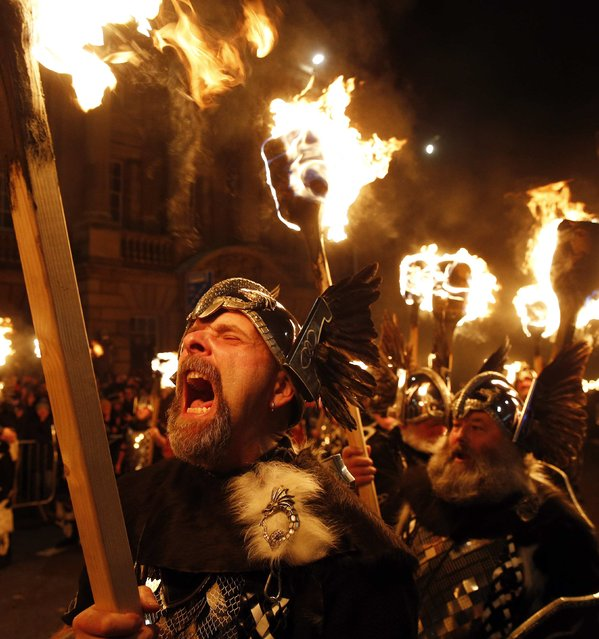 Up Helly Aa vikings from the Shetland Islands hold lit torches during the annual torchlight procession to mark the start of Hogmanay (New Year) celebrations in Edinburgh, Scotland December 30, 2014. (Photo by Russell Cheyne/Reuters)