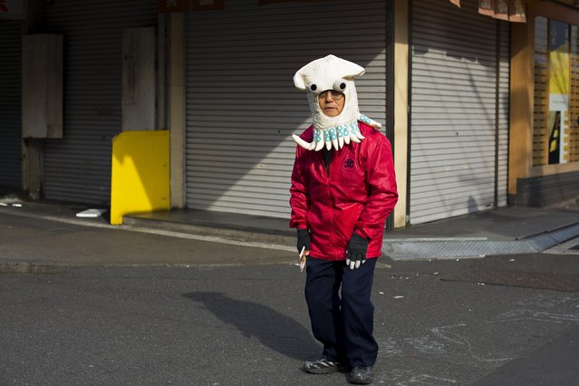 A man, who distributes discount vouchers for a nearby restaurant, wears a hat in the shape of an octopus at the outer part of the Tsukiji fish market, the Jogai Shijo, in Tokyo January 4, 2015. (Photo by Thomas Peter/Reuters)