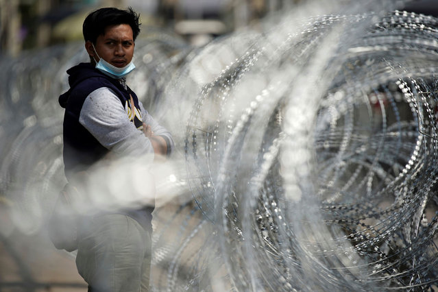 A migrant worker stands next to barbed wire in front of a closed shrimp market, amid the coronavirus disease (COVID-19) outbreak, in Samut Sakhon province, in Thailand, December 20, 2020. (Photo by Athit Perawongmetha/Reuters)
