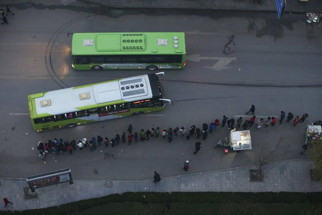 People wait for a bus to take them to Beijing from Yanjiao, Hebei province, China November 13, 2015. Beijing, home to more than 21 million residents, is in the midst of launching itself into a mega-city where 110 million will live, served by new links to the port city of Tianjin and neighbouring Hebei province. (Photo by Jason Lee/Reuters)