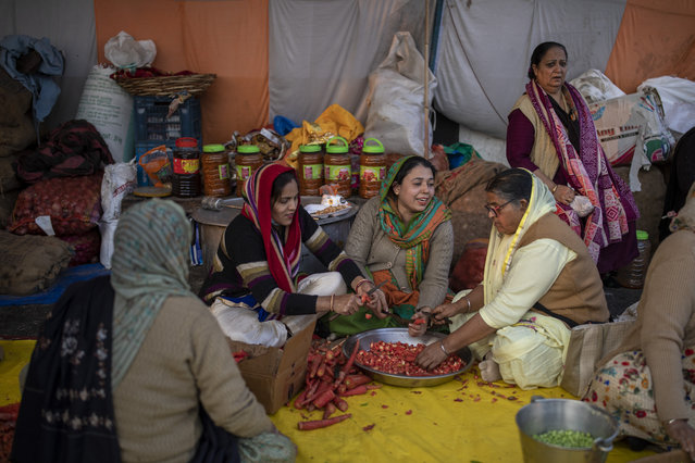 Family members of farmers prepare food for fellow farmers as they block a highway in protest against new farm laws at the Delhi-Uttar Pradesh state border, on the outskirts of New Delhi, India, Monday, January 11, 2021. (Photo by Altaf Qadri/AP Photo)