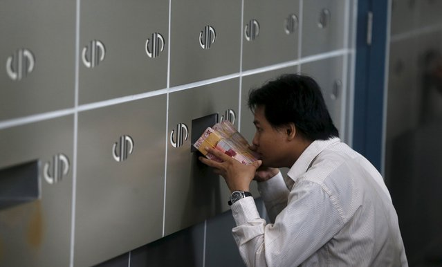 An employee of a money changer passes a stack of Indonesia rupiah notes through small window to his  colleague in Jakarta, in this October 8, 2015 file photo. Indonesia's foreign currency reserves have doubled in size in the eight years since the global financial crisis roiled its markets but an examination by Reuters of its reserve assets shows a thinner buffer than officially reported data on gross reserves suggests. (Photo by Reuters/Beawiharta)