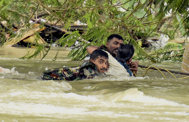 Indian army soldiers rescue a man from flood waters in Chennai, India, Thursday, December 3, 2015. The heaviest rainfall in more than 100 years has devastated swathes of the southern Indian state of Tamil Nadu, with thousands forced to leave their submerged homes and schools, offices and a regional airport shut for a second day Thursday. (Photo by R. Senthil Kumar/Press Trust of India via AP Photo)