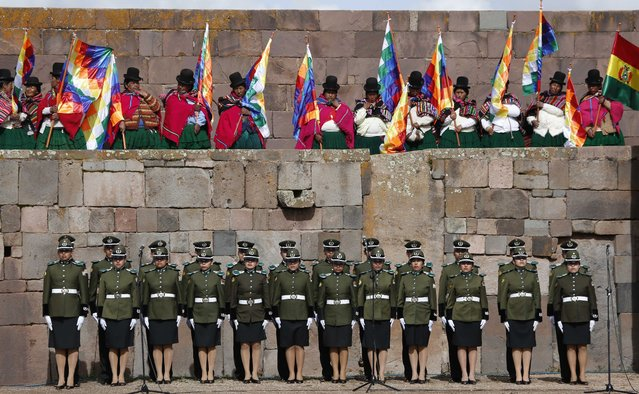 Supporters of Bolivia's President Evo Morales look over a Bolivian police unit during a ceremonial swearing-in, led by Aymaran spiritual guides at the archeological site Tiwanaku, Bolivia, Wednesday, January 21, 2015. (Photo by Juan Karita/AP Photo)