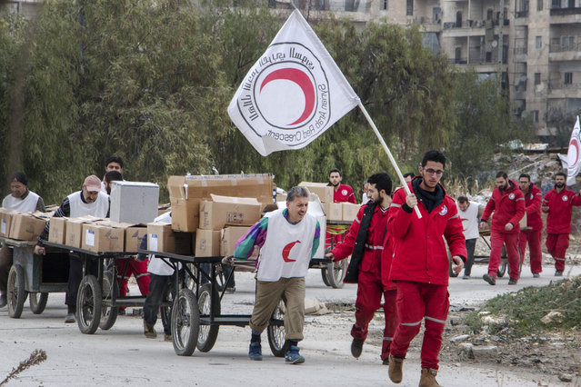 Members of the Syrian Red Crescent escort Syrians and aid supplies from a rebel-controlled area to a regime held area of the northern Syrian city of Aleppo on December 10, 2015 through the Garage al-Hajz crossing in the Bustan al-Qasr district. (Photo by Karam Al-Masri/AFP Photo)