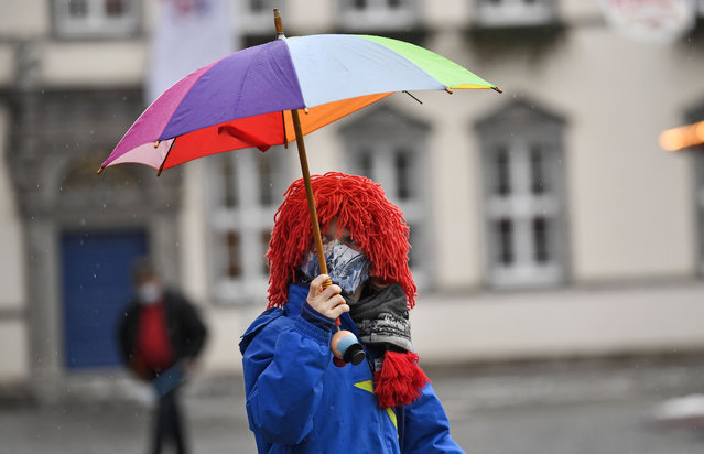 A young carnival reveller dressed as a clown holds an umbrella in the empty old town in Duesseldorf, Germany, Monday, February 15, 2021. (Photo by Martin Meissner/AP Photo)