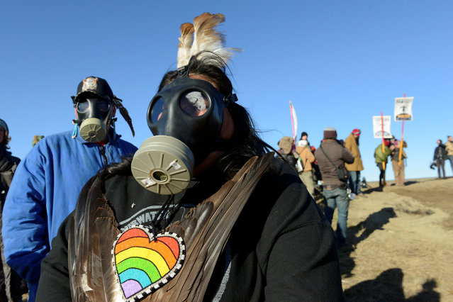 People wear gas masks next to the pipeline route during a protest against the Dakota Access pipeline near the Standing Rock Indian Reservation in St. Anthony, North Dakota, U.S. November 11, 2016. (Photo by Stephanie Keith/Reuters)