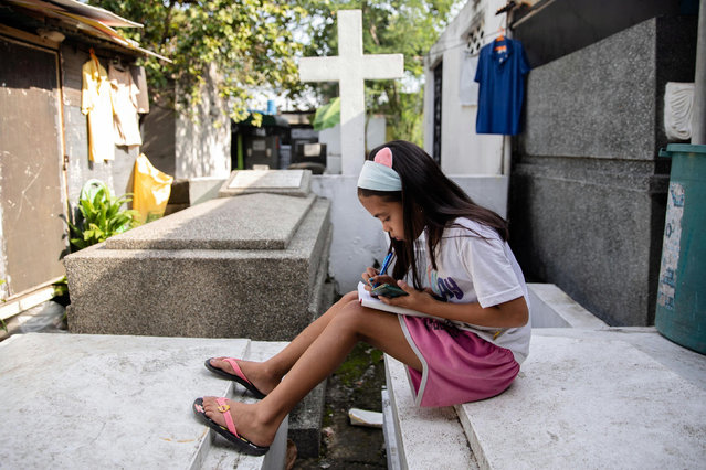 Grade 5 student Lovely Joy De Castro, 11, takes notes while attending an online class using a smartphone, as schools remain closed during the Coronavirus disease (COVID-19) outbreak, at Manila South Cemetery where she lives with her family in Makati City, Philippines, November 6, 2020. (Photo by Eloisa Lopez/Reuters)