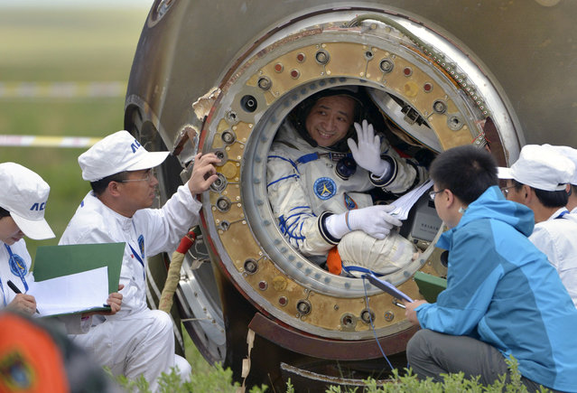 Chinese astronaut Nie Haisheng waves before stepping out of the re-entry capsule of China's Shenzhou-10 spacecraft after it landed in Inner Mongolia Autonomous Region, on June 26, 2013. Three Chinese astronauts returned to Earth on Wednesday, touching down after a successful 15-day mission in which they docked with a space laboratory. (Photo by Reuters/China Daily via The Atlantic)