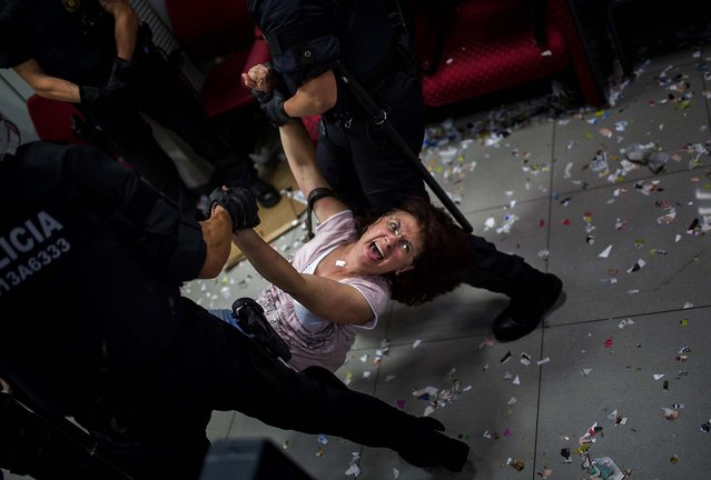 An activist of the Mortgage Victims' Platform is carried by police officers after occupying a bank as part of a protest to support a neighbor who is facing an eviction process in Barcelona, on July 10, 2013. With 26 percent unemployment, Spain is struggling to emerge from its second recession in just over three years as the economy battles to recover from the collapse of its once-booming real estate sector. (Photo by Emilio Morenatti/Associated Press)