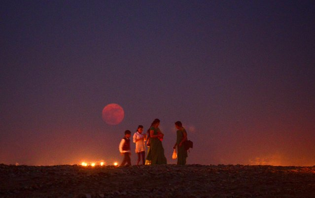 """Indian people walk at Sangam as the """"supermoon"""" rises in Allahabad on November 14, 2016. Skygazers headed to high-rise buildings, ancient forts and beaches on November 14 to witness the closest """"supermoon"""" to Earth in almost seven decades, hoping for dramatic photos and spectacular surf. The moon will be the closest to Earth since 1948 at a distance of 356,509 kilometres (221,524 miles), creating what NASA described as """"an extra-supermoon"""". (Photo by Sanjay Kanojia/AFP Photo)"""