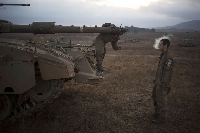 An Israeli soldier checks the barrel of a tank of the 53rd Armor Battalion during an exercise in the Israeli controlled Golan Heights near the border with Syria, early Thursday, July 18, 2013. (Photo by Ariel Schalit/AP Photo)