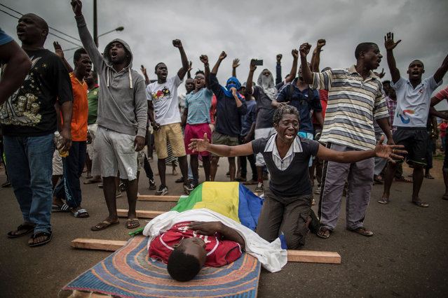 A woman cries over the body of Axel Messa, 30, wrapped in the flag of Gabon as he is laying on the ground in a street of the Libreville district of Nzeng Ayong on September 2, 2016. His mother told AFP he was shot in front of his home on September 1, 2016 night. Two men died after overnight clashes in Gabon's capital Libreville between security forces and demonstrators protesting President Ali Bongo's announced victory in a disputed election, witnesses and an AFP journalists said on September 2, 2016. The latest deaths take the toll up to five killed since riots and protests broke out on August 31, 2016 after Bongo was declared the winner of the weekend presidential vote by a razor-thin margin. (Photo by Marco Longari/AFP Photo)
