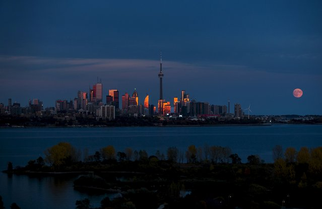 The moon rises behind the skyline in Toronto, October 26, 2015. (Photo by Mark Blinch/Reuters)
