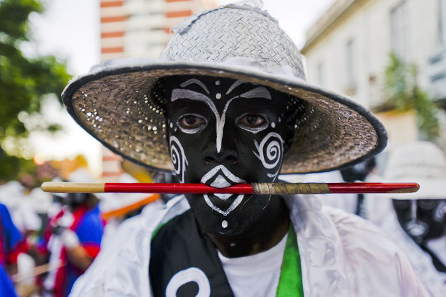 """A costumed drummer holds a drum stick in his mouth has he performs at """"Las Llamadas"""" parade during Carnival celebrations in Montevideo, Uruguay, Friday, February 6, 2015. (Photo by Matilde Campodonico/AP Photo)"""